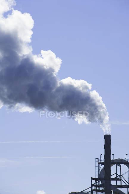 Cheminée industrielle avec nuages de fumée de centrale électrique contre ciel bleu — Photo de stock