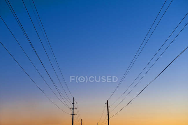 Low angle view of power lines and poles against blue and orange sky at sunset — Foto stock