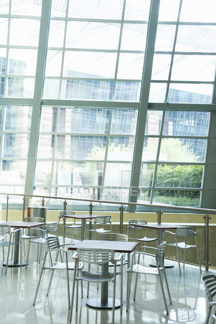 Cafe tables in spacious office building with large windows — Stock Photo