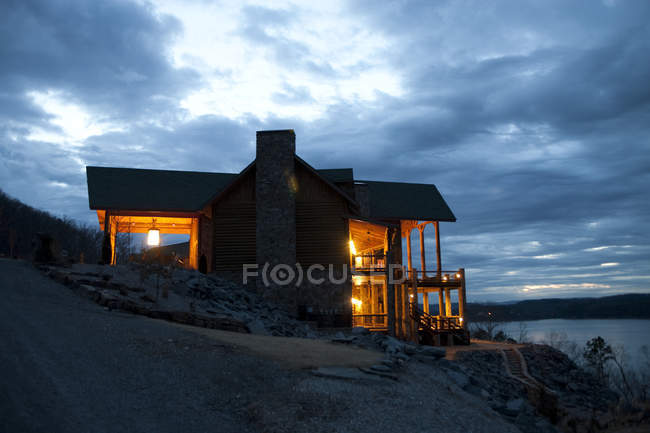 Hotel do campo que negligencia o lago na noite — Fotografia de Stock