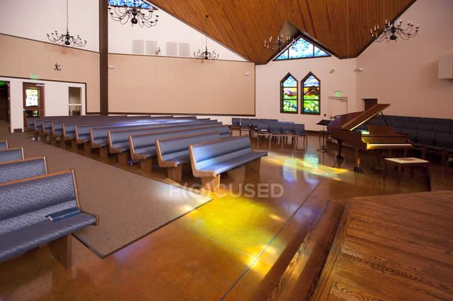 Пустая церковь со скамьями и богато украшенными окнами — стоковое фото