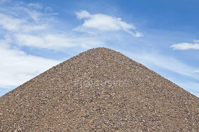 Gravel pile against blue sky with white clouds — Stock Photo