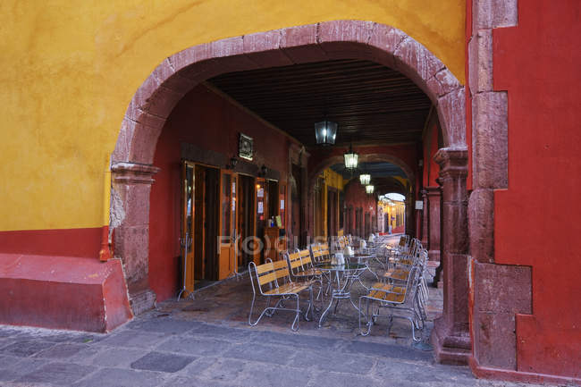 Old world colonnade with cafe tables and chairs, San Miguel de Allende, Guanajuato, Mexico — стокове фото