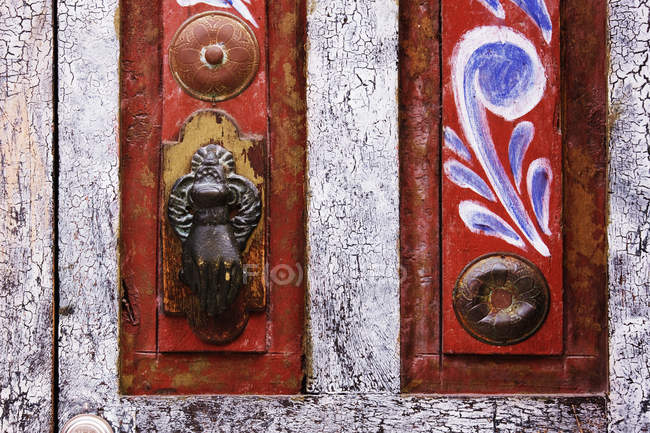 Close-up of rustic door with vintage handle and painting — Stock Photo