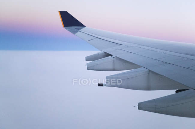 Wing and engines of jet aircraft in flight at dawn — Stock Photo