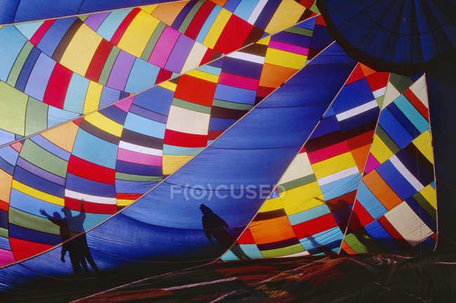 Inflating colorful hot air balloon and silhouettes of people in Texas, USA — Stock Photo