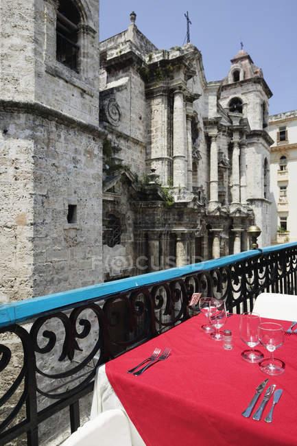 Tabela do café com a cutelaria que negligencia a catedral antiga, Havana, Cuba — Fotografia de Stock