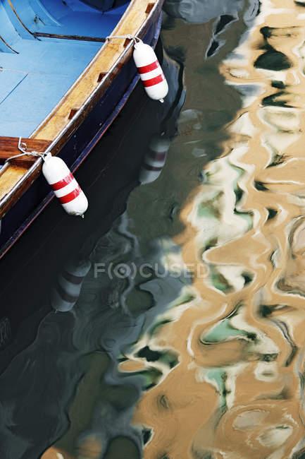 Солнечный свет и лодка, отражающая в канале Венеции в Италии, Европе — стоковое фото