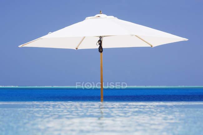 Open beach umbrella in water of resort in Bora Bora, French Polynesia — Stock Photo