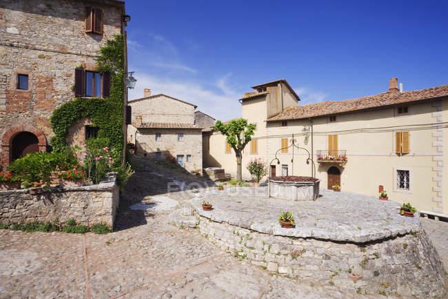 Деревня площади и хорошо в Рокка dOrcia в Италии, Европе — стоковое фото