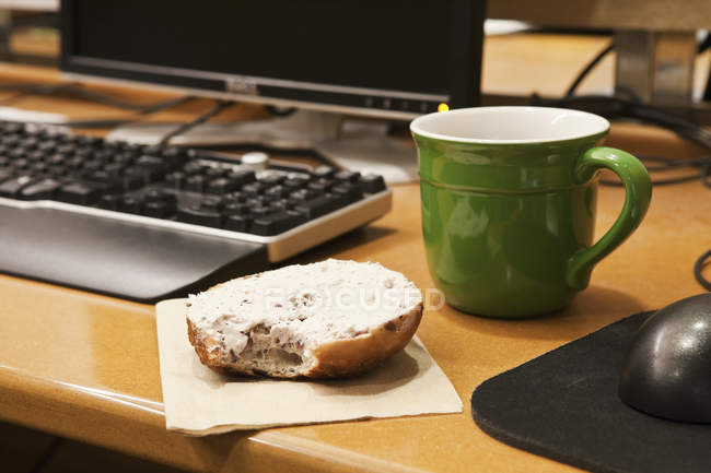 Close-up of coffee cup and bagel on work desk — Stock Photo