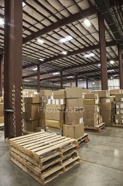 Boîtes en carton et palettes en entrepôt — Photo de stock