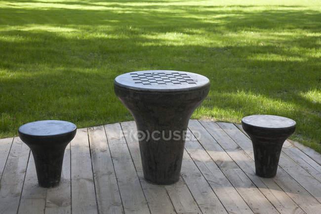 Фігурний шаховий стіл і табуретки на дерев'яній палубі в міському парку — стокове фото