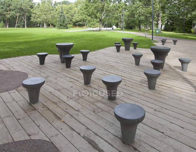 Фігурні шахові столи та табурети на дерев'яній палубі в міському парку — стокове фото