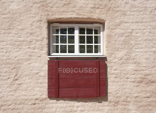 Facciata tradizionale con finestra protetta con griglia e persiane in legno — Foto stock