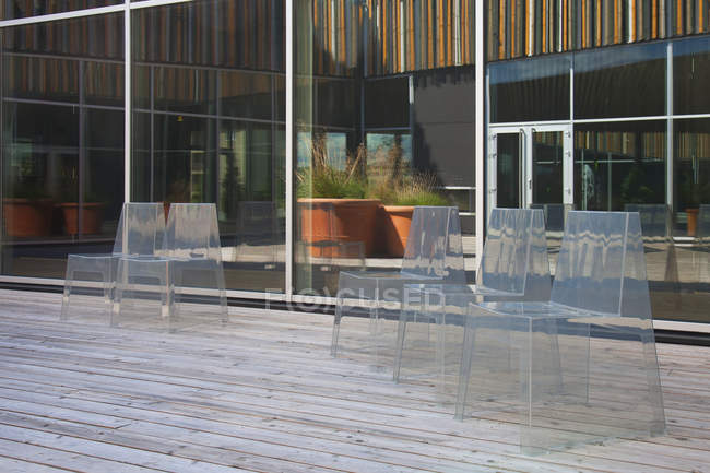 Row of modern translucent chairs on wooden flooring by large windows — Stock Photo