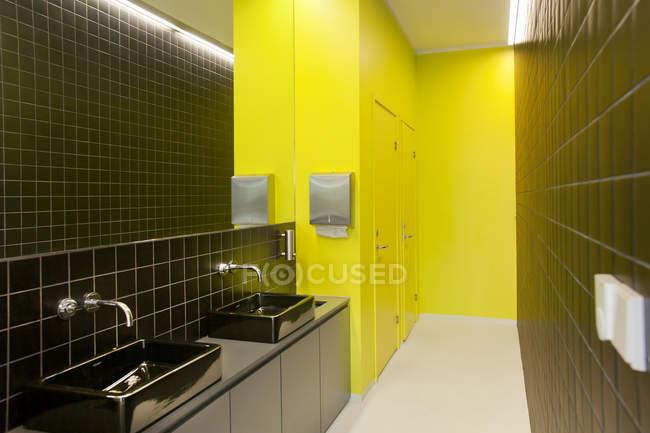 Bagno contemporaneo con eleganti piastrelle nere e pareti gialle — Foto stock