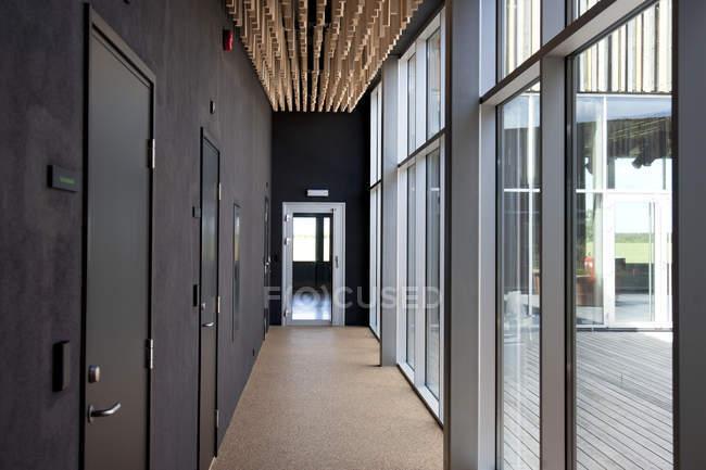 Moderno corridoio ufficio con grandi finestre e parete con porte — Foto stock