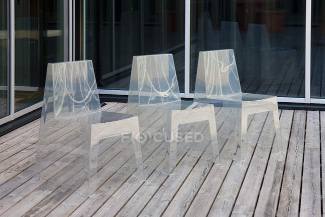 Row of modern translucent chairs on wooden flooring — Stock Photo
