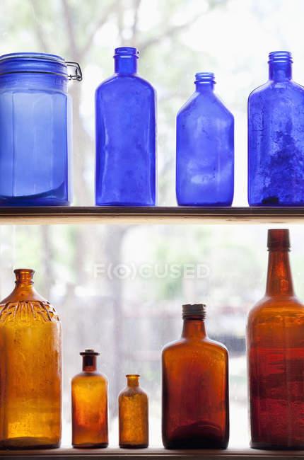 Bouteilles antiques empilées dans des rangées sur des étagères par la fenêtre — Photo de stock