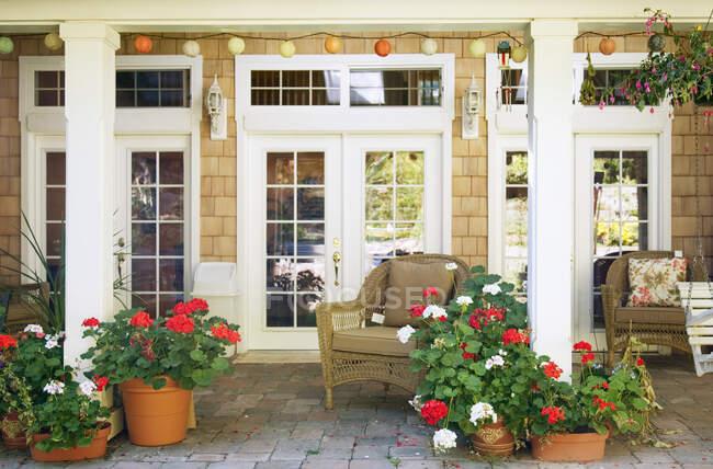 Тераса в саду з стільцями й рослинами. — стокове фото