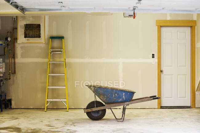 Carriola blu e scala in garage — Foto stock