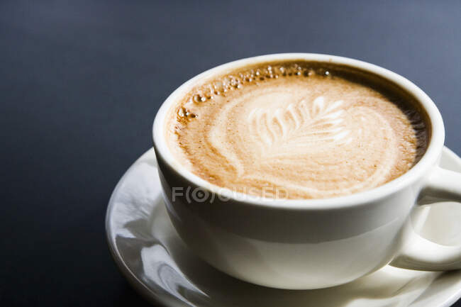 Leaf design in espresso foam, close-up view of white cup on black background — Stock Photo