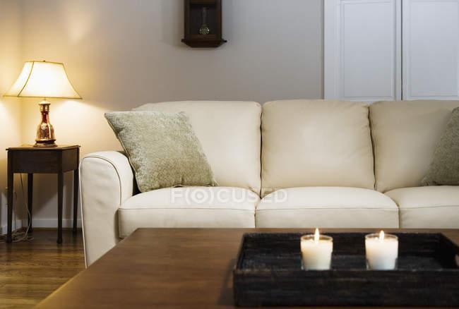 Свечи, зажженные на подносе в гостиной в современном интерьере апартаментов — стоковое фото