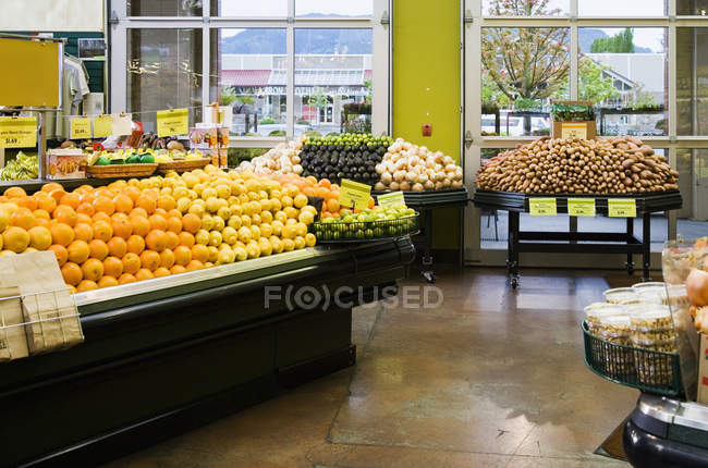 Fresh produce on shelves and display in grocery store — Stock Photo