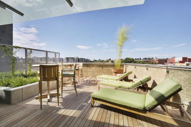 Шезлонги на балконі на даху в сучасному багатоквартирному будинку — стокове фото