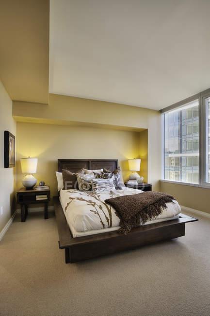 Luxury bedroom in modern highrise apartment — Fotografia de Stock
