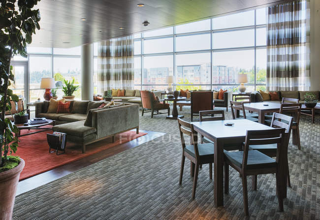 Clubhouse tables and seats in highrise hotel — Stock Photo