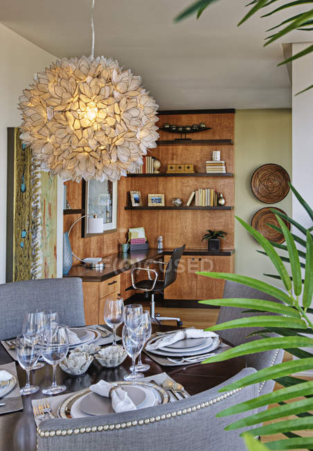 Chandelier over luxury dining room table in highrise apartment — Stock Photo