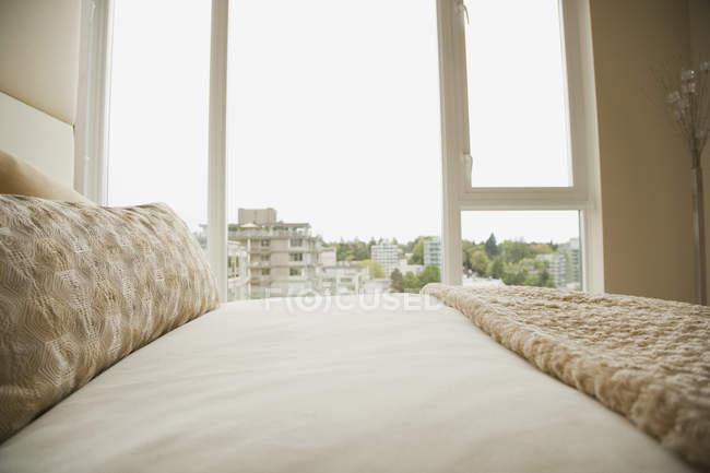 Монохромная спальня в бежевом с городом за окном — стоковое фото