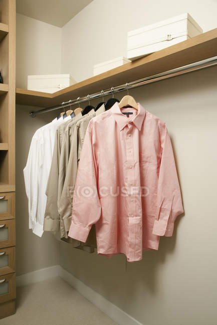 Closet inside with hanging shirts in apartment — стокове фото