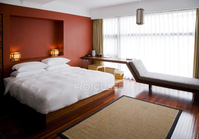 Современная спальня с подоконником и белыми постельными принадлежностями — стоковое фото