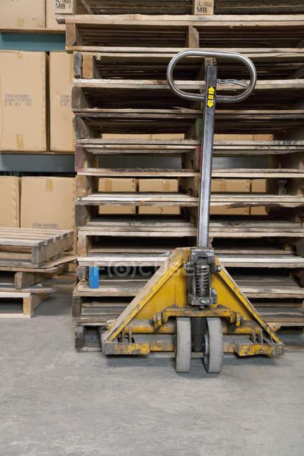 Camion de main et palettes en bois dans l'usine — Photo de stock