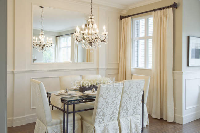 Luxury dining room with chairs, table and hanging chandelier — Fotografia de Stock