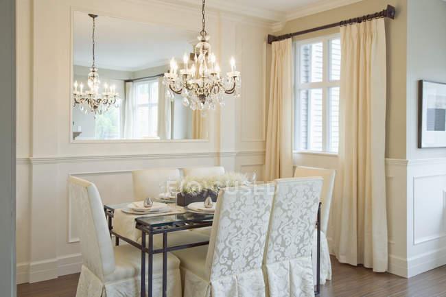 Sala de jantar luxuosa com cadeiras, tabela e candelabro de suspensão — Fotografia de Stock