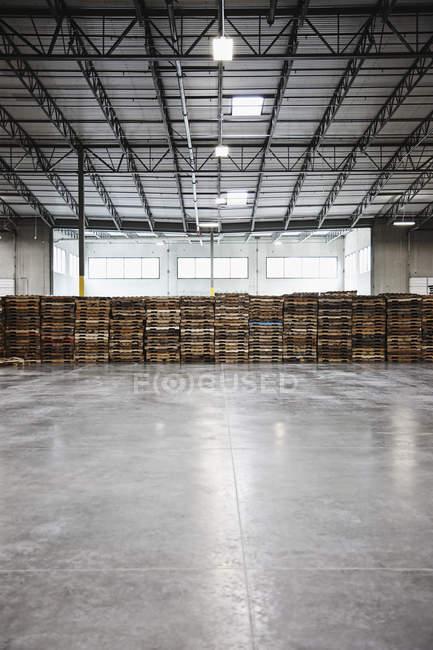 Palettes empilées dans l'intérieur d'entrepôt, Sumner, Washington, Etats-Unis — Photo de stock