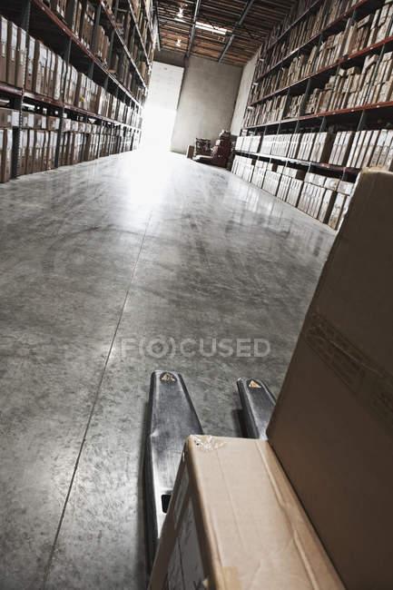 Boîtes en carton sur chariot élévateur dans l'entrepôt — Photo de stock