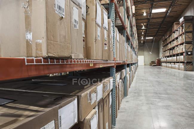 Boîtes en carton sur des étagères dans l'entrepôt — Photo de stock