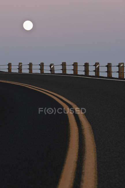 Luna piena su strada curva con linee gialle al crepuscolo — Foto stock