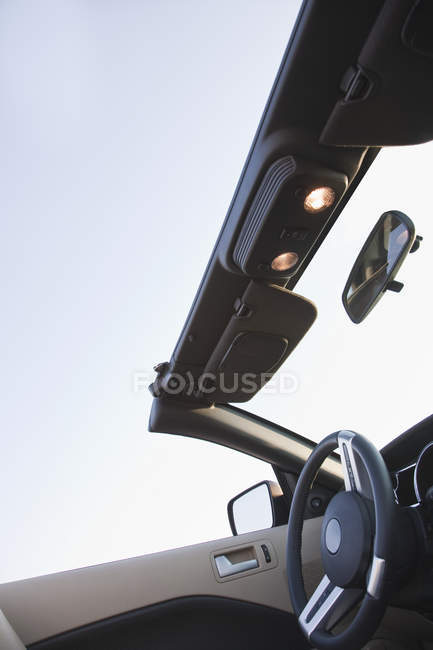 Steering wheel and roof of convertible vehicle, cropped — стоковое фото