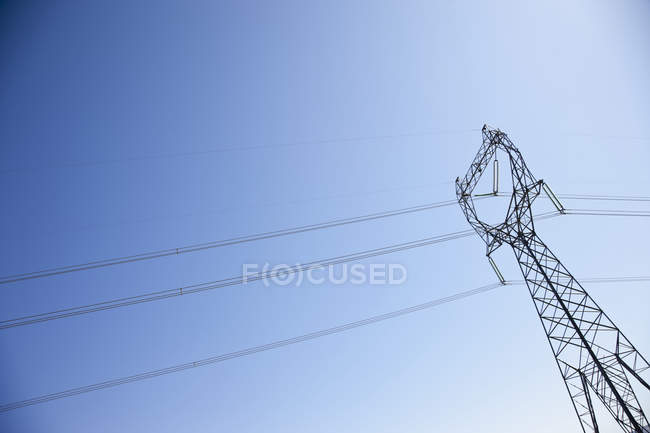 Pilón eléctrico con líneas eléctricas contra el cielo azul - foto de stock