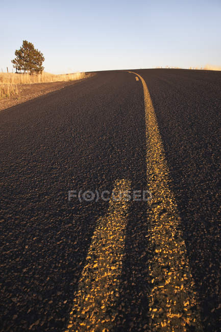 Two lane highway road in country field — стокове фото