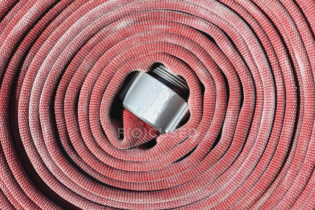 Coiled red fire hose, close-up — Stock Photo