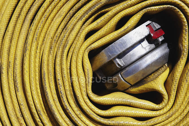 Coiled yellow fire hose, close-up — Stock Photo