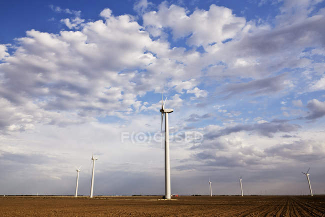 Countryside wind farm with rotating turbines in field — Stock Photo