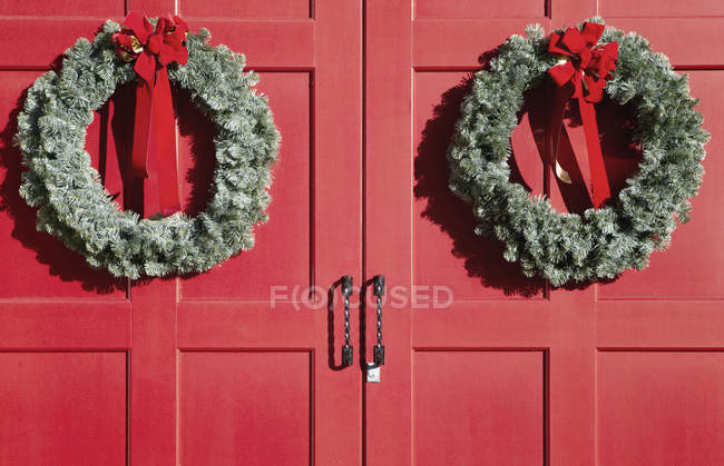 Christmas wreaths hanging on red doors — Stock Photo